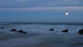 Sorgere della luna sopra una riva rocciosa fotografia stock