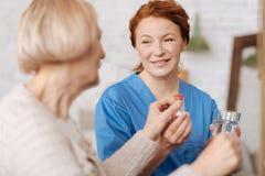Sorgfältige Krankenschwester, ihrer geduldigen nehmenden Medizin vergewissernd lizenzfreie stockbilder