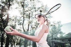 Sorgfältiger attraktiver weiblicher Spieler, der Tennistechnik vervollkommnet stockfotos