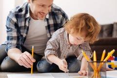 Sorgfältiger Junge beim Zeichnen des Kreises auf dem Entwurf Lizenzfreie Stockfotos