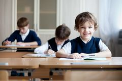 Sorgfältiger Student, der am Schreibtisch, Klassenzimmer sitzt Stockbild