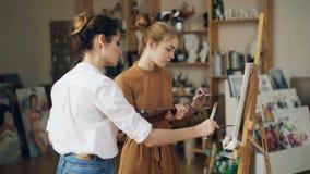 Sorgfältiger Student malt Bild unter der Anleitung des Berufskünstlers zusammenarbeitend im modernen Studio Frau ist stock video