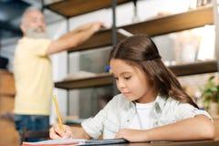 Sorgfältiges kleines Mädchen, das ihre Hauptaufgabe tut stockbild