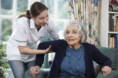 Sorgfalt-Arbeitskraft, die älterer Frau hilft, aus Stuhl heraus aufzustehen stockbild