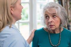 Sorgfalt-Arbeitskraft, die zu Hause mit deprimierter älterer Frau spricht Lizenzfreies Stockfoto