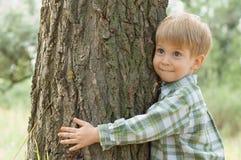 Sorgfalt der Natur - Umarmung des kleinen Jungen ein Baum Lizenzfreies Stockbild