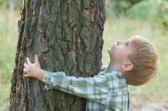 Sorgfalt der Natur - Umarmung des kleinen Jungen ein Baum Stockbild