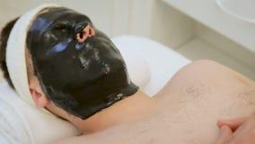 Sorgfalt f?r die Haut der M?nner im Badekurort Cosmetologist tut die Gesichtsreinigung, kosmetische Gesichtsmaske und Hautpflege  stock video