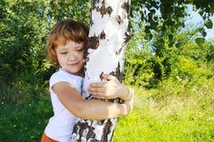 Sorgfalt für Natur - Umarmung des kleinen Mädchens ein Baum Stockfotografie