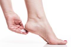 Sorgfalt für trockene Haut auf den gut-gepflegten Füßen und Fersen mit sahnt Lizenzfreie Stockfotografie