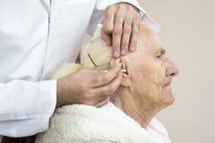 Sorgfalt und Krankenpflege von alten Leuten Säubern der Ohren mit einem Stock lizenzfreie stockfotos