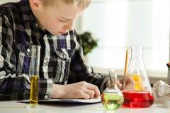 Sorgfältiger Junge, der seine Wissenschaftshausarbeit tut Lizenzfreie Stockfotografie