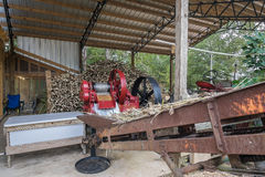 Sorghum Cane Mill. This is the third stage of the molasses making process. The cane is fed through the red sorghum mill.  The mill is powered by a tractor with Stock Images