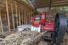 Sorghum Cane Mill. This is the third stage of the molasses making process. The cane is fed through the red sorghum mill.  The mill is powered by a tractor with Royalty Free Stock Photography