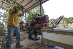 Sorghum Mill. A man feeding a sorghum mill. The mill is powered using a PTO shaft between its flywheel gears and a tractor.  The cane juice flows into the Royalty Free Stock Photos