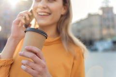 Sorglose blonde Frau, die Getränk während des Gespräches genießt Stockbild
