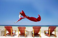 Sorglose Frau, die am Strand springt stockfotografie
