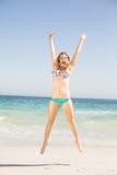 Sorglose Frau im Bikini, der auf den Strand springt Stockfotografie