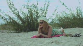 Sorglose Frau im Sommerkleid, das am Strand sich entspannt stock footage