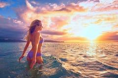 Sorglose Frau im Sonnenuntergang auf dem Strand Schöner Sonnenuntergang Lizenzfreie Stockbilder