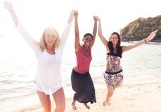 Sorglose Frauen, die den Strand genießen Stockfotografie