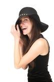 Sorglose junge Frau, die mit schwarzem Hut lacht Lizenzfreie Stockfotos
