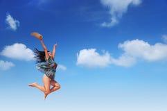 Sorglose junge Frau springt in den Himmel Stockbilder