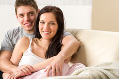 Sorglose junge Paare, die auf Couch umfassen Lizenzfreie Stockfotografie