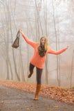 Sorglose Modefrau, die im Herbstpark sich entspannt Stockfoto