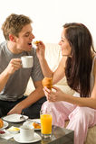 Sorglose Paare, die Frühstück in den Pyjamas essen Stockbilder