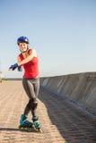 Sorglose sportliche blonde Aufstellung mit Inline-Rochen Lizenzfreies Stockbild