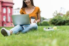 Sorglose Studentin, die auf Notizbuch auf Gras schreibt Lizenzfreies Stockfoto