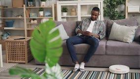 Sorgloser Afroamerikanermann benutzt den Roboterstaubsauger, der auf Sofa sitzt und das Smartphonegenießen hält stock footage