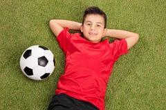 Sorgloser Junge in einem roten Fußballtrikot, das auf Gras liegt Lizenzfreies Stockfoto