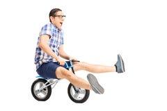 Sorgloser junger Kerl, der ein kleines Fahrrad reitet Stockfotos