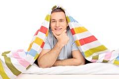 Sorgloser junger Mann, der im Bett bedeckt mit Decke liegt Stockbilder