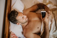 Sorgloser Kerl, der neuen Tag genießt Hübscher junger Mann im Bett schreibend am Handy, Textnachricht sendend oder Nummer wählend stockfoto