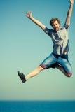 Sorgloser Mann, der durch Seeozeanwasser springt Stockfotos