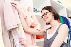Sorgloser weiblicher Kunde, der Stoff im Shop wählt Stockbilder