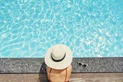 Sorgloses Frauenentspannung im Swimmingpool-Sommerferienkonzept stockfotos