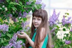 Sorgloses Mädchen steht in einer blühenden Flieder Lizenzfreies Stockfoto