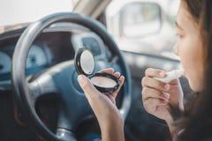 Sorgsenhet chauffören klibbades i trafik kvinnachaufför som applicerar makeup genom att använda backspegeln i bilen och tala på royaltyfri foto