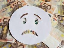sorgsenhetemoticon på vit och bakgrund med eurosedlar royaltyfri foto