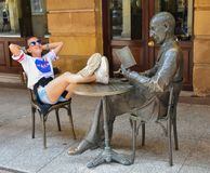 Soria, Spain; 06 24 2019: impolite teenage girl putting her feet on the table of bronze statue of a poet reading a book in front. Of a cafe. The girl has her stock image