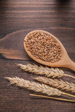 Sorns in wooden spoon and ears of wheat on old. Board vertical version food and drink concept Royalty Free Stock Images