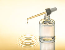 Soro hidratando para a pele seca, fundo amarelo, pipeta com gota, respingo Foto de Stock Royalty Free