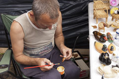 Sorochinskaya Fair.  Man decorates crafts. Stock Photography