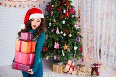 Sorprenda a la mujer hermosa joven con los regalos cerca de un árbol de navidad Año Nuevo Imagen de archivo
