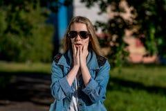 Sorprenden al adolescente Verano en el parque en el aire fresco Un día soleado brillante en gafas de sol Gesto con el suyo Foto de archivo