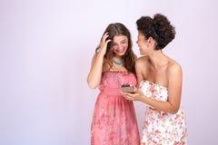 Sorprenden a dos novias que se divierten y cuando miran su smartphone Tecnología, Internet, comunicación Imagen de archivo libre de regalías
